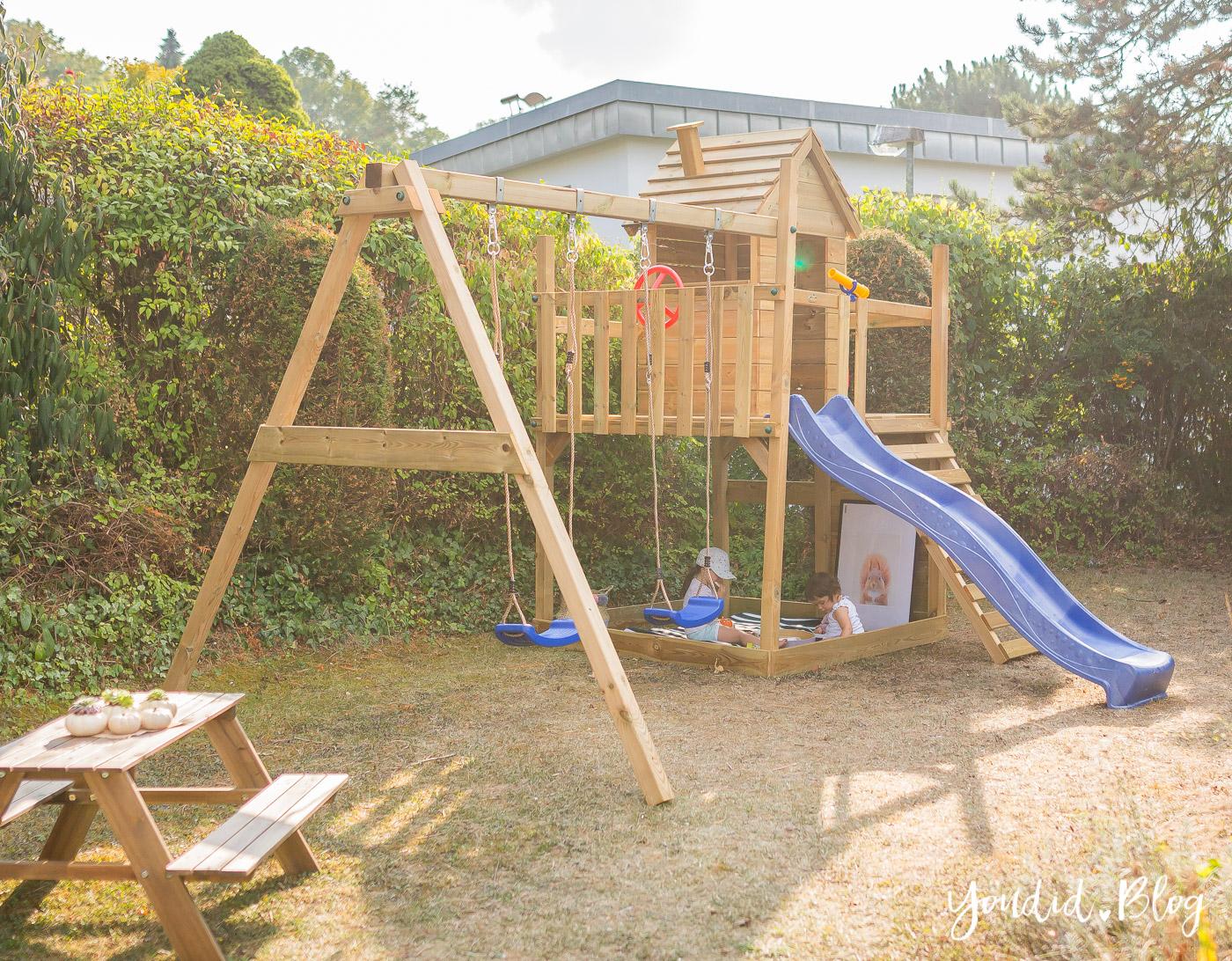 Ein Kletterturm mit Rutsche, Sandkasten, Schaukel und Spielhaus ...